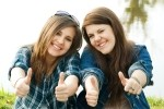 two girls giving thumbs up sign
