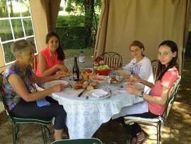 american girl and french girl on adolesco exchange have lunch with french grandmother at the table